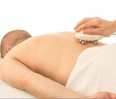 Picture of a man getting a massage with a massage tool