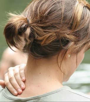 Woman holding her neck because she has neck pain due to a whiplash injury in a car accident